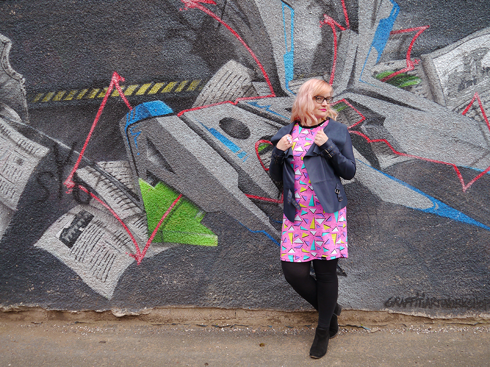 Dreamland Duplex print dress, Saved by the Bell style, pom pom earrings, Alternate Normality candyfloss hairclip, River Island leather jacket, street style with graffiti