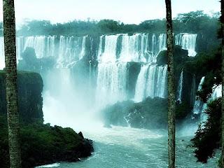 Ilha San Martin e Salto San Martin, Parque Nacional de Iguazú, Argentina. Ilha, à esquerda. Quedas d'água, ao fundo, vistas entre duas palmeiras.