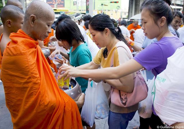 Moine buddhiste recevant des dons à Bangkok