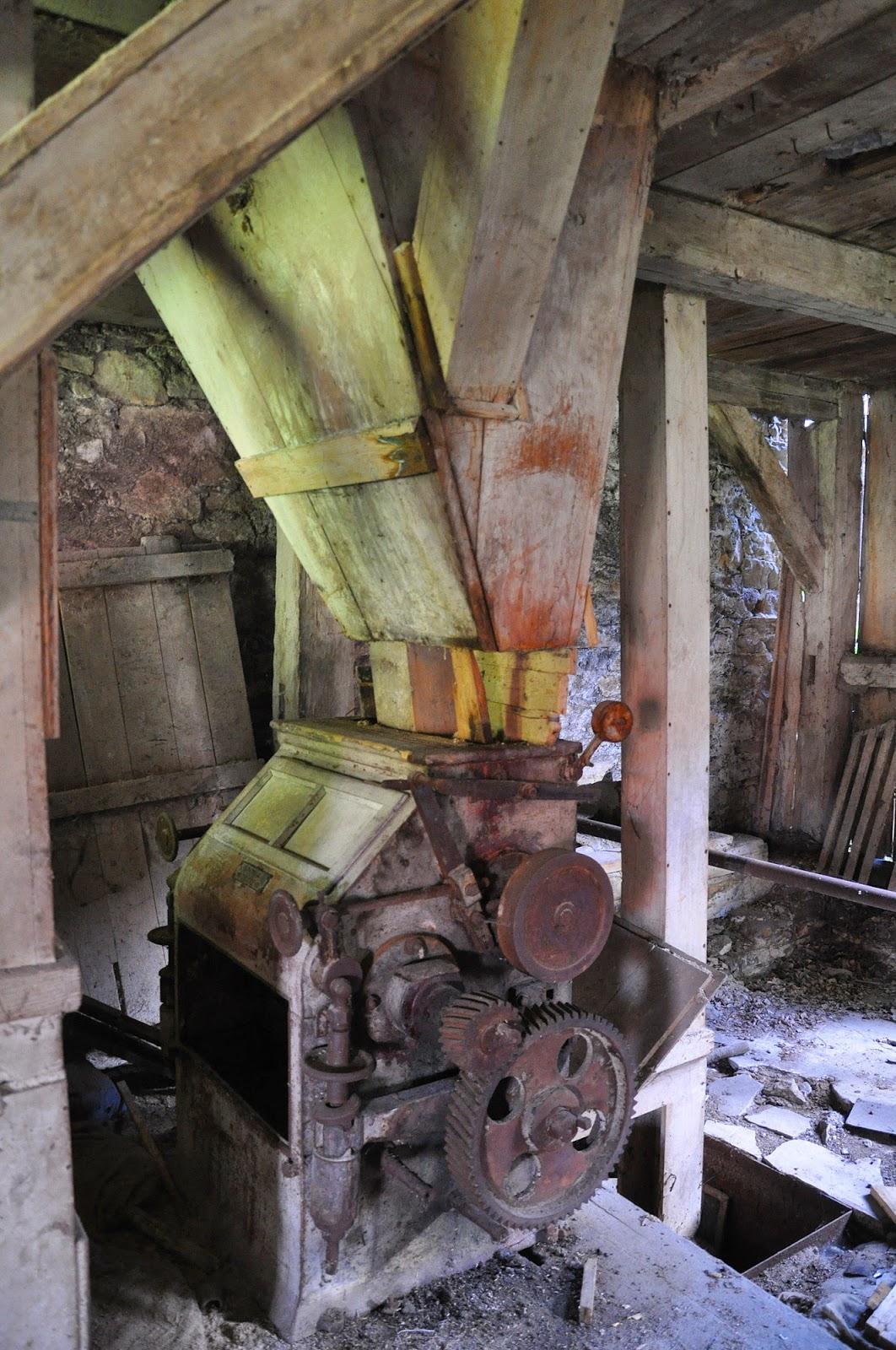 """Wnętrze młyna - parter. Od strony południowej znajdowała się taka """"maszyna"""" do przemiału - tu ze zbliżeniem tabliczki. Czerwiec 2014, foto. KW."""