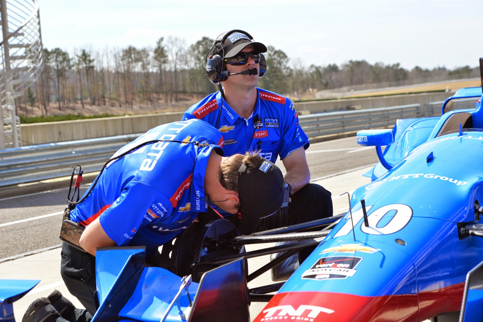 Engineers on Tony Kanaan's NTT Data Chip Ganassi Chevrolet look over his wheel during Tuesday's Open Test
