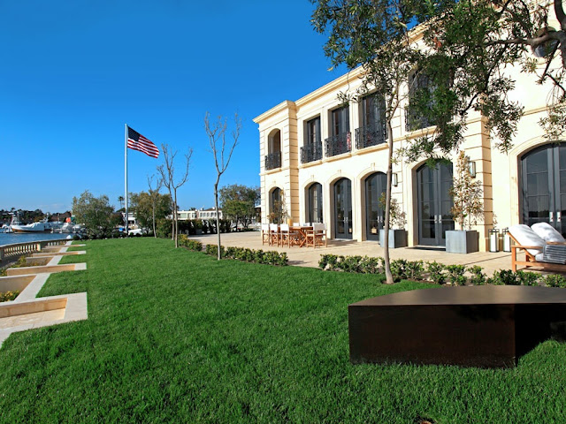 exterior of a french limestone mansion on harbor island in newport beach with a lawn, flag pole, outdoor table and deck chair