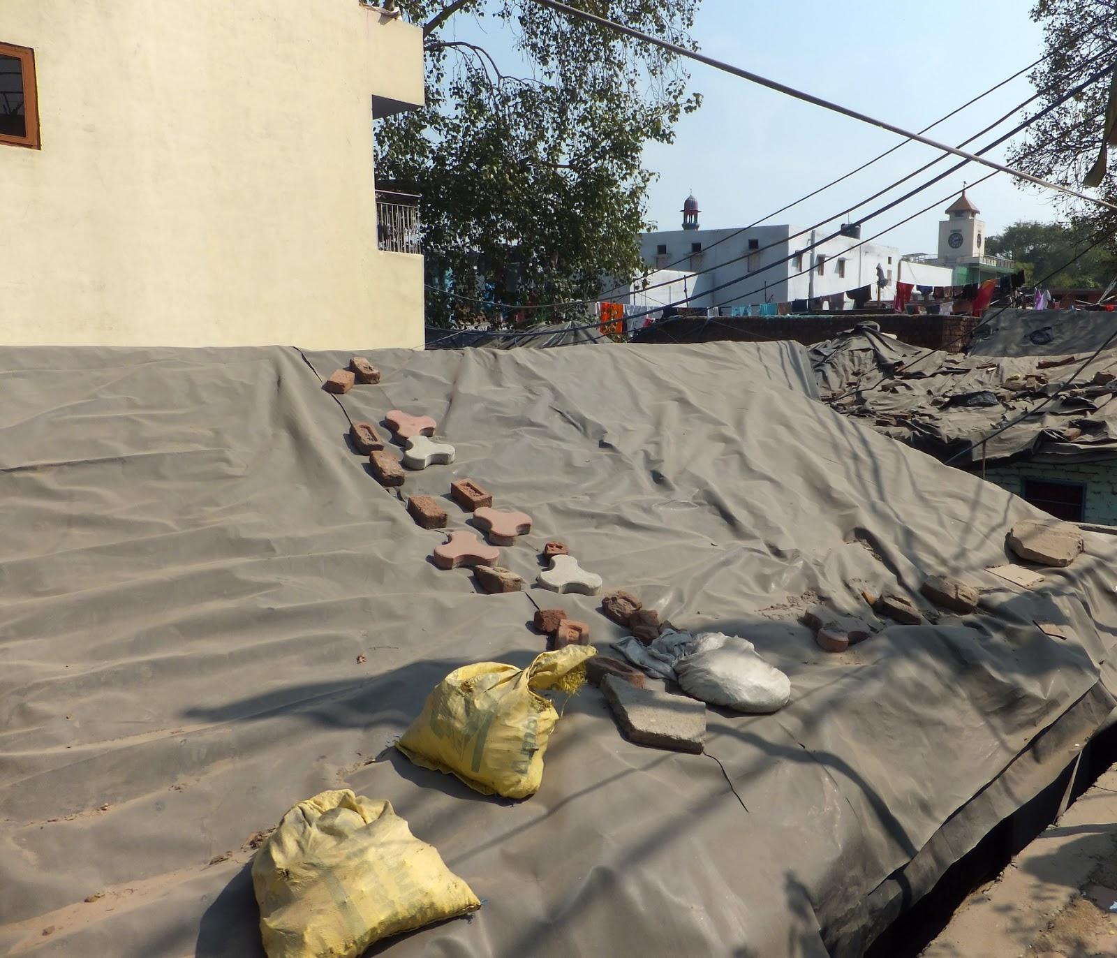 крыша покрытая брезентом и заваленная тротуарной плиткой и мешками с песком