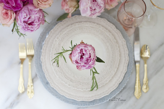 Lace dishes with peonies and gold flatware on marble