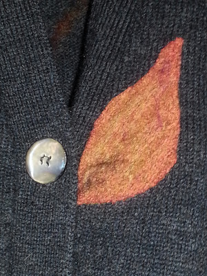 closeup of adecorated felted leaf on the sweater