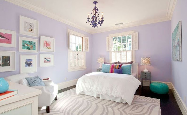 Girls bedroom with small chandelier, lavender wall, grey and white zebra print rug, white bedding with colorful accent pillows
