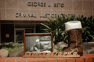 A photo, boots and hat of Dr. Beto displayed outside the criminal justice center.