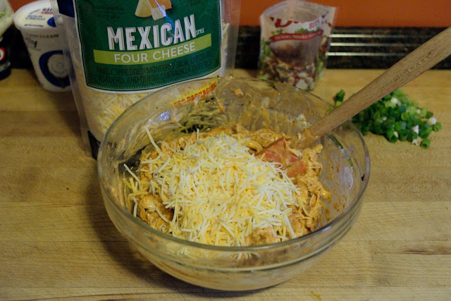 A picture of the shredded cheese being added to the bowl of chicken mixture.