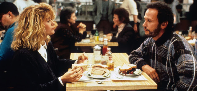 Meg Ryan and Billy Crystal in When Harry Met Sally (1989). Image shows Sally and Harry seated in Katz's Delicatessen after the . She is holding a sandwich after just finishing faking an orgasm while he looks on embarrassed.