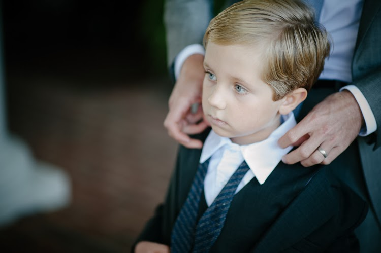 ring bearer putting on his bow tie