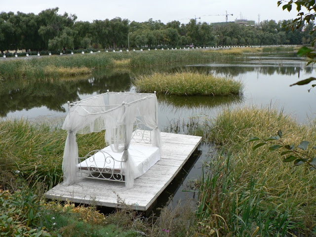 wedding bed set on a platform in a lake