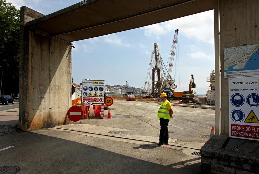 Entarda para a zona portuária com um trabalhador em primeiro plano e os guindastes ao fundo