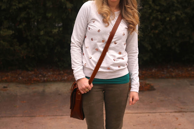 Sequined sweatshirt paired with camo pants and booties