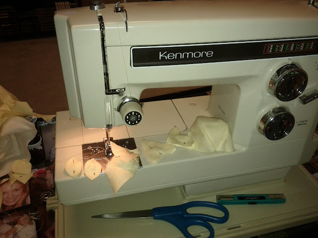 Many small pieces of yellow fabric lie on a table and sewing machine.  Several are pinned with white and black pins and there is a pair of blue scissors and a green seam ripper on the table as well.