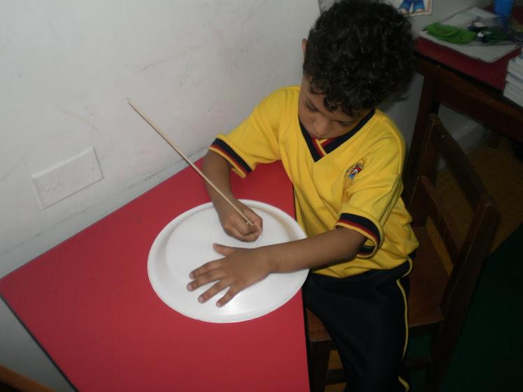 Puyando y haciendo el trazo correcto del fonema b en platos de icopor