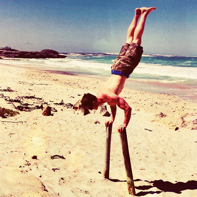 Tim Stevenson performing calisthenics on the beach