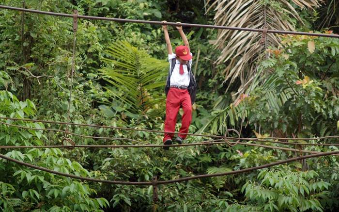 A boy climbs a wire across a river to get to school in Pintu Gabang, Indonesia. These children have to tightrope walk 30 feet above a flowing river to get to their class on time and then walk a further seven miles through the forest to their school in the town of Padang...Picture: Panjalu Images / Barcroft Media