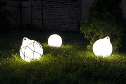 Оригинальные светильники на траве в темном саду