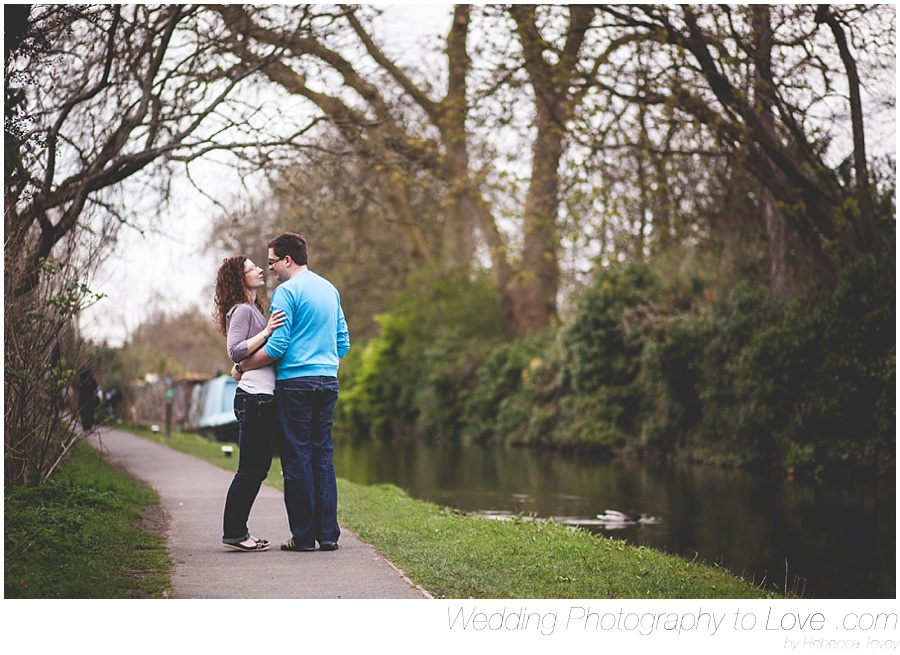couple kiss by a river in oxford for engagement photos before wedding