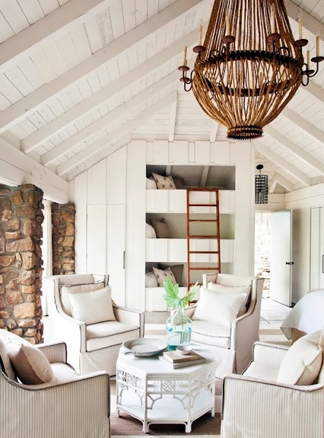 sitting area in a lakeside cottage bedroom with vaulted ceilings, a large chandelier, four arm chairs surrounding an white octagon table, built into the wall there are three  bunk beds,