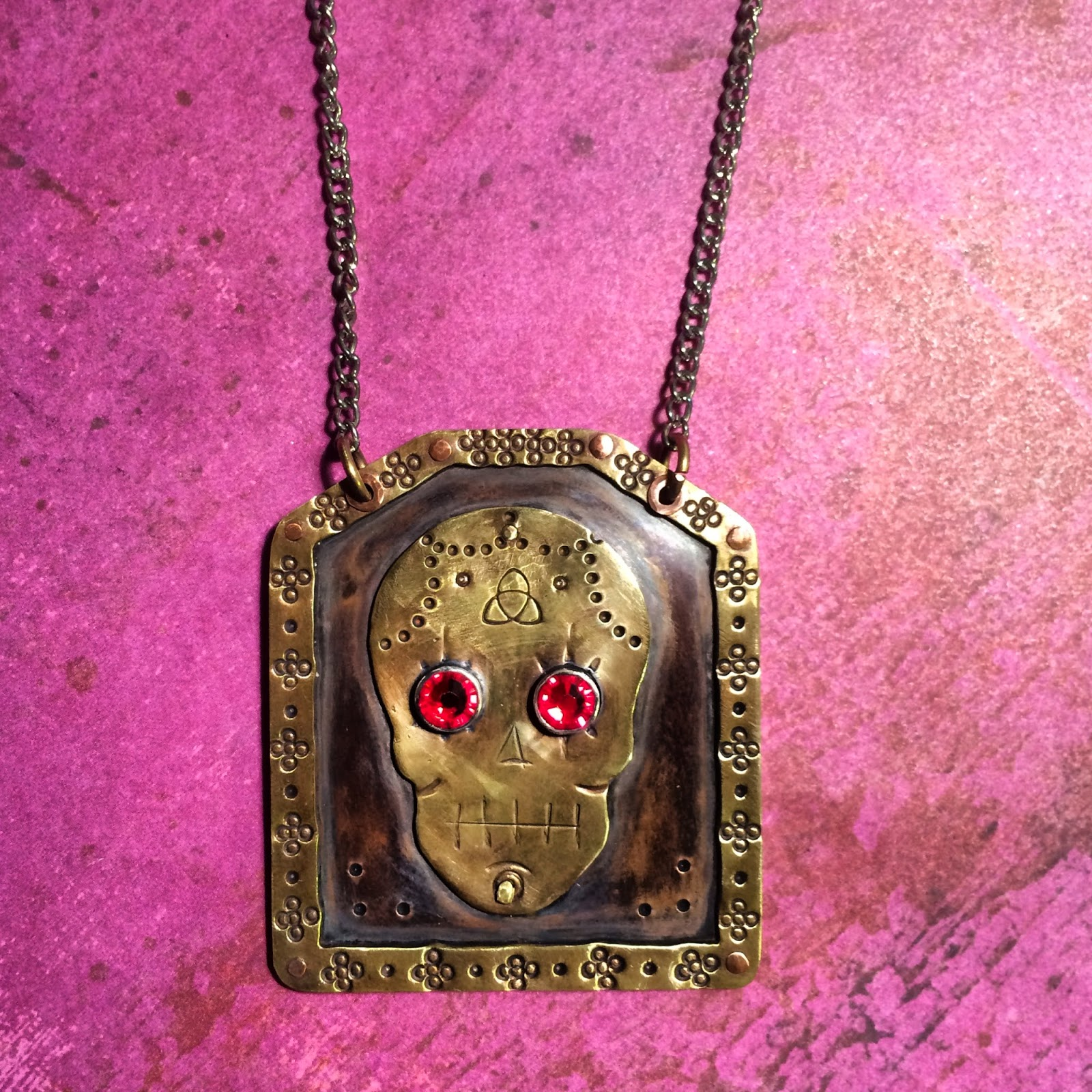 Necklace made out of brass and copper using soldering and cold connection techniques. Day of the dead necklace with texture and red eyes