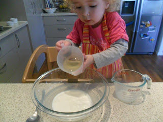 Carefully adding oil to dry ingredients for strawberry muffins recipe