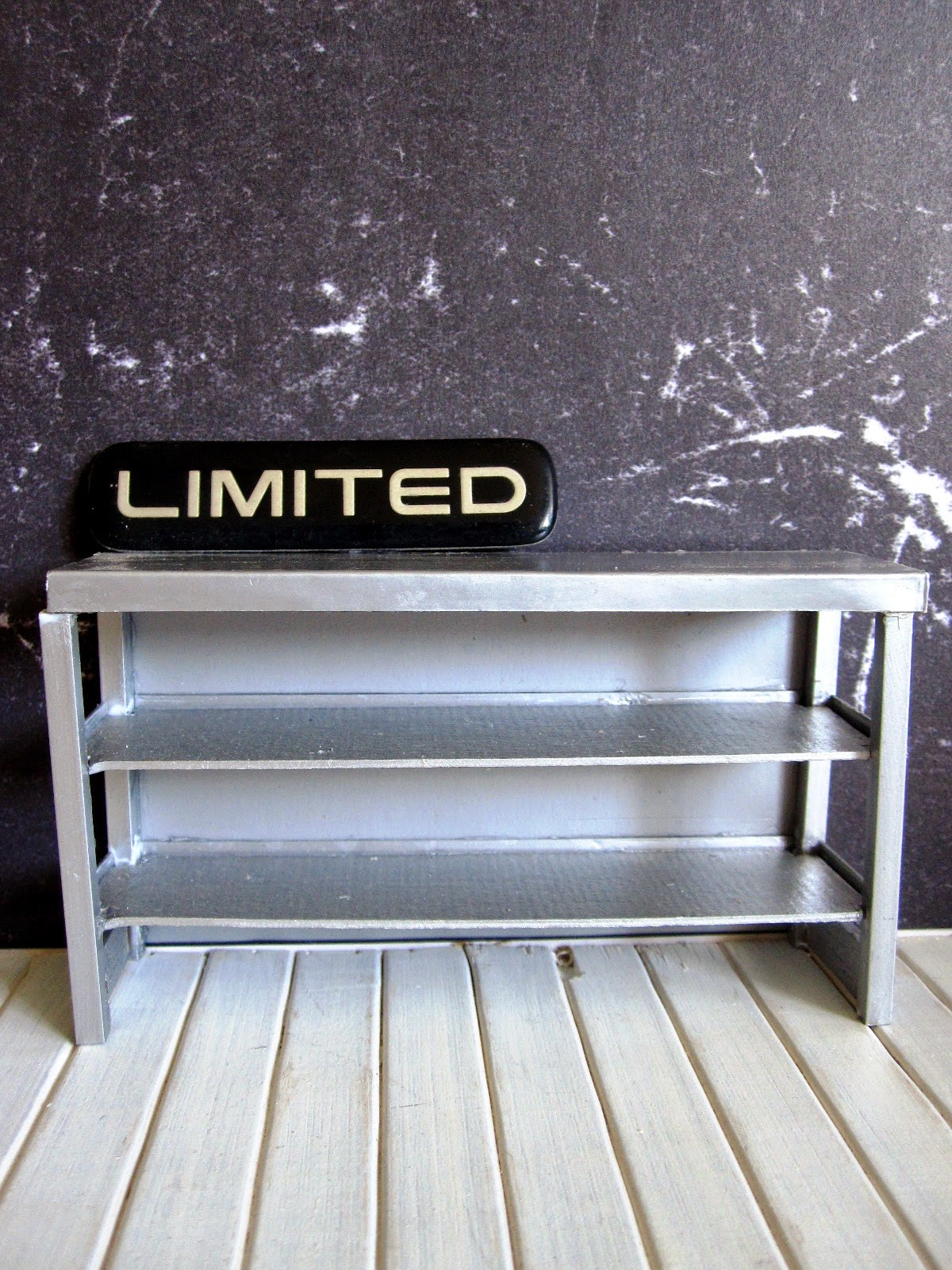 Modern doll's house miniature industrial grey storage bench in front of a wall covered with black marble-patterned paper. On the bench is a sign saying 'Limited'.