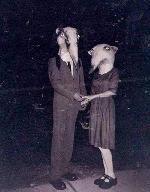 A man and a woman stand outdoors, both wearing large animal masks.