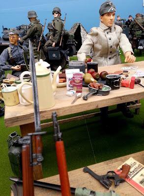 1/6 scale German soldier sitting at a table with food on it in diorama of an army post on display at a scale model exhibition.
