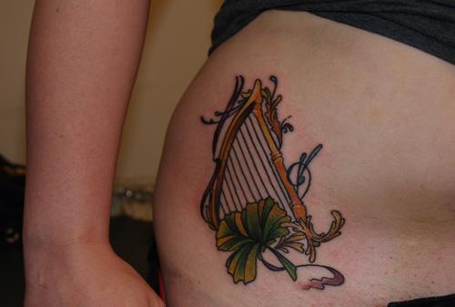 chica con tatuaje celta del arpa en la cadera
