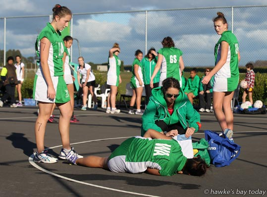 Mahinaarangi Cooper, slight ankle sprain, tended by Samantha Scheyvens, assistant coach, Maniapoto, game against Hawke's Bay - under-17 netball at Hawke's Bay Regional Sports Park, Hastings photograph