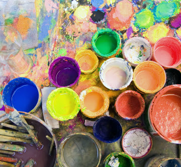 open used multicolored cans of paint and brushes sitting on painted abstract canvas