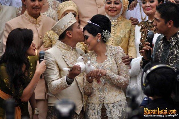 foto Pernikahan Anang dan Ashanty mencium kening sambil lepas burung merpati