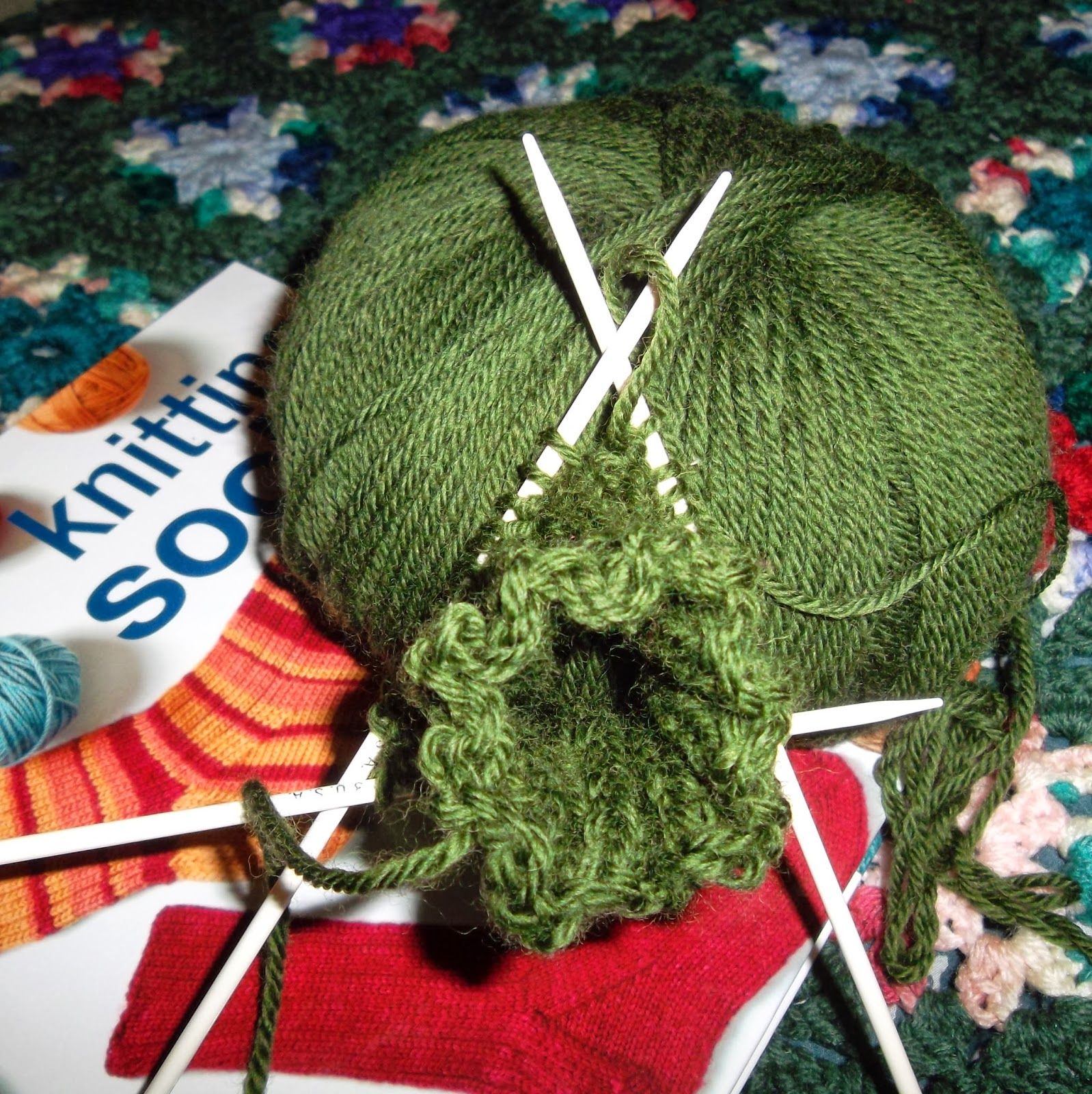 "Ball of dark green yarn and sock-sized circular knitting on double-pointed needles with a book, ""Getting Started Knitting Socks"" by Ann Budd"