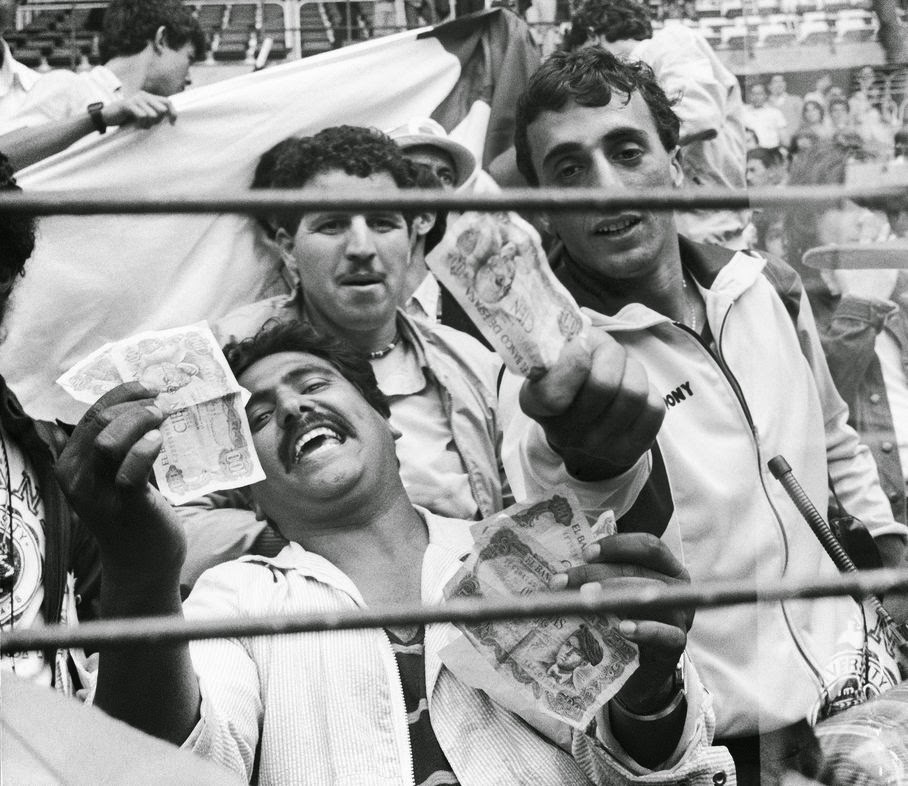 In this June 25, 1982 file photo, Algerian soccer supporters show money to photographers, in Gijon, Spain, after the World Cup soccer match between West Germany and Austria. On this day: West Germany beat Austria 1-0, a result that meant both teams progressed to the next round at Algeria's expense. After West Germany took an early lead, the game ran its bland course to conclusion to the ire of the watching Algerians.