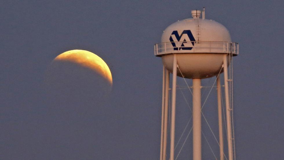 Лунное затмение на фоне водонапорной башни больницы ранним утром в среду, 8 октября 2014 в Джексоне, штат Миссисипи, США