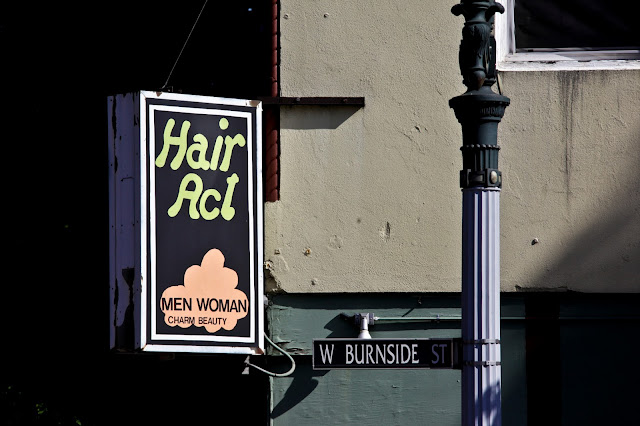 A sign on a hair place in Portland that says 'Men Woman'.