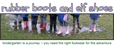 Kids standing in a rain puddle all wearing rubber boots