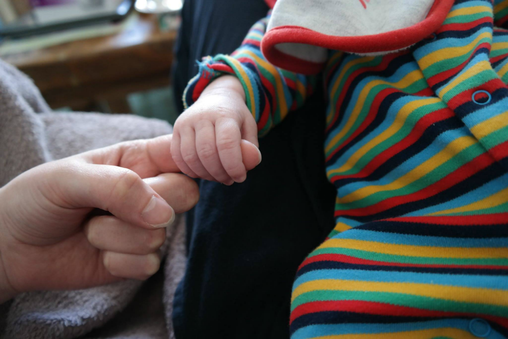Tiny baby hand gripping mum's finger