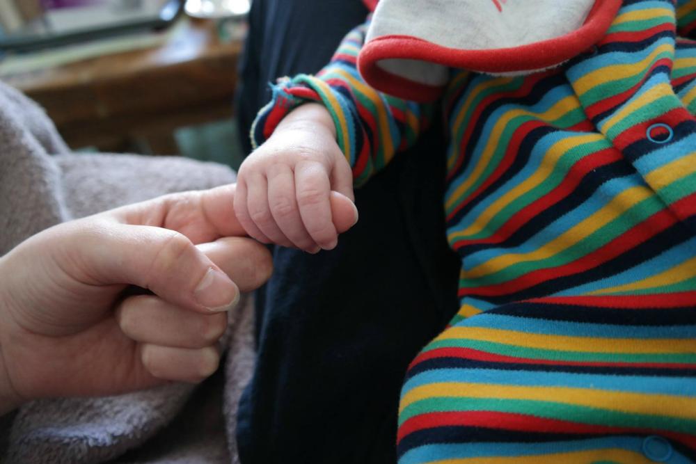 Tiny baby hand gripping mum's finger