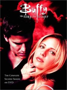 Cover art for S2 of Buffy the Vampire Slayer, featuring Buffy and Angel against a red background. Angel looks like he's thinking about biting Buffy's throat, while she looks directly into the camera.