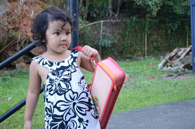 Kecil carrying a pink rectangular case