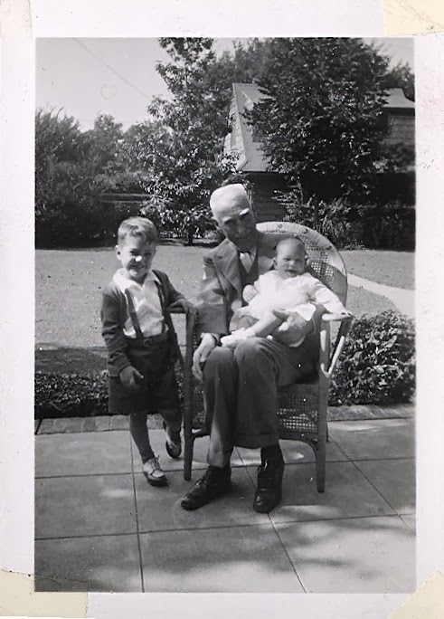 A very elderly man holds a young baby in his lap, while a little boy stands close by.