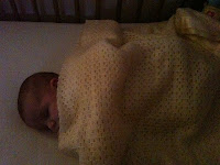 baby sleeping under a yellow cellular blanket in a cot
