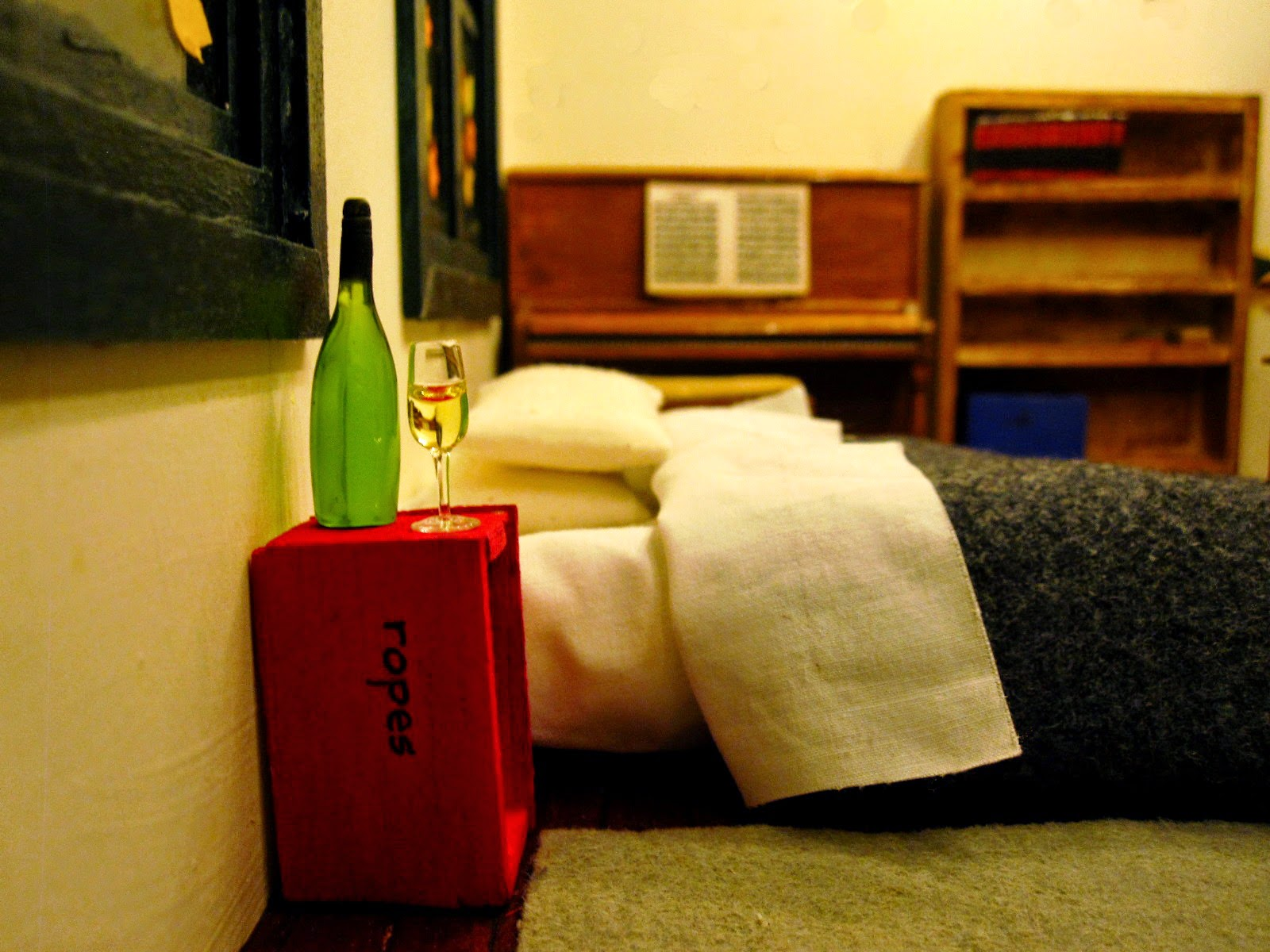 Miniature scene with a mattress and bedding on the floor, a red crate marked 'ropes' next to it with a glass and bottle of wine on it, and a piano in the background.