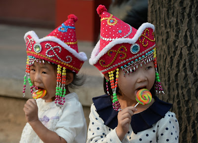 "TOPSHOTS Young Chinese tourists eat lollipops during their visit to Tiananmen Square in Beijing on October 3, 2013.  Chinese tourists should not pick their noses in public, pee in pools or steal airplane life jackets, China's image-conscious authorities have warned in a handbook in their latest effort to counter unruly behaviour. The National Tourism Administration publicised its 64-page Guidebook for Civilised Tourism -- with illustrations to accompany its list of dos and don'ts -- on its website ahead of a ""Golden Week"" public holiday that started on October 1."