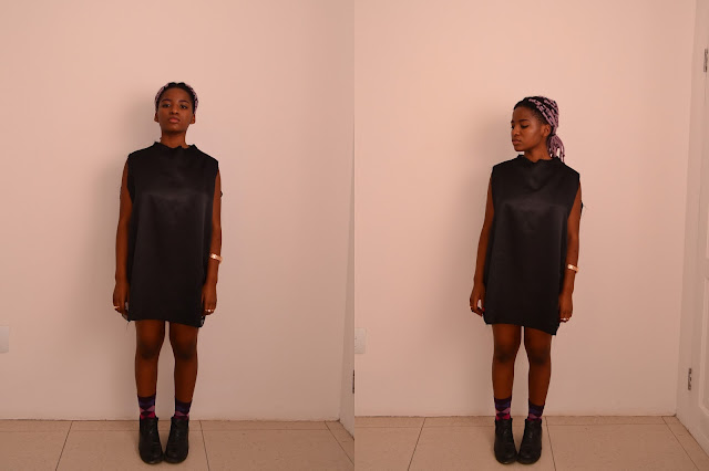 black girl with purple yarn braids in a satin t-shirt dress