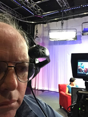 "William Elliott in headphones behind his camera as the crew prepare to record the 9th episode of ""Members Only"" for CMAC Television in downtown Fresno CA."