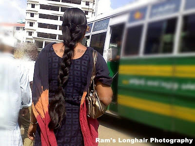 Long hair braided angel standing before a bus.