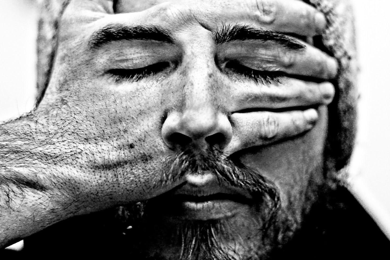 Fotografía artística en blanco y negro de un hombre con la mano sobre su cara y sobre el dorso de la mano están los ojos cerrados.